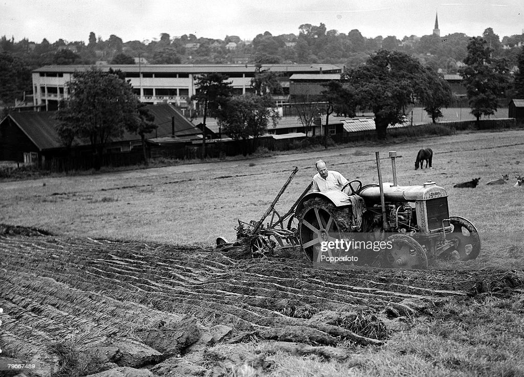 London, England, 17th July, 1940, A man ploughing up the field in his tractor at the car parks of Wimbledon Tennis Club for food production as part of the war effort in World War Two