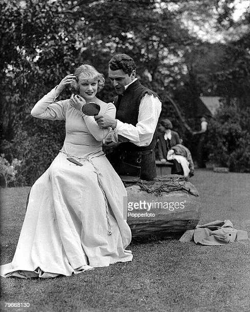London England 18th May Actor Jack Hawkins rehearsing his role as Orlando in the Shakespeare play As You Like It whilst helping Anna Neagle to make...