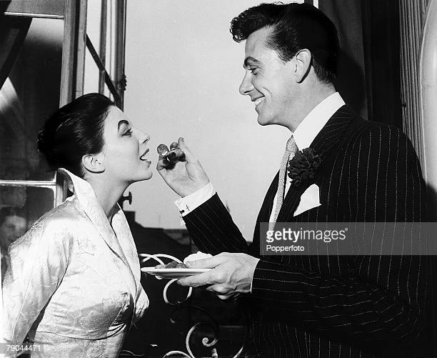 London England 25th May 1952 British Actor Maxwell Reed and actress Joan Collins enjoy strawberries and cream at their wedding reception