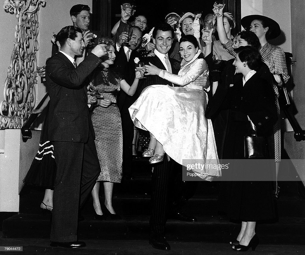 London, England. 25th May 1952. British Actor Maxwell Reed carries his new bride, actress Joan Collins down the stairs surrounded by guests after their wedding. : News Photo