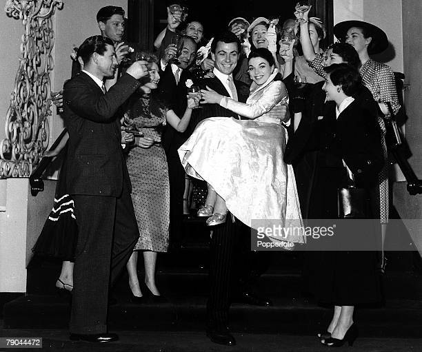 London England 25th May 1952 British Actor Maxwell Reed carries his new bride actress Joan Collins down the stairs surrounded by guests after their...