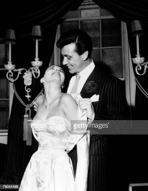 London England 25th May 1952 British Actor Maxwell Reed helps his new wife actress Joan Collins remove the satin bolero style jacket that she wore...