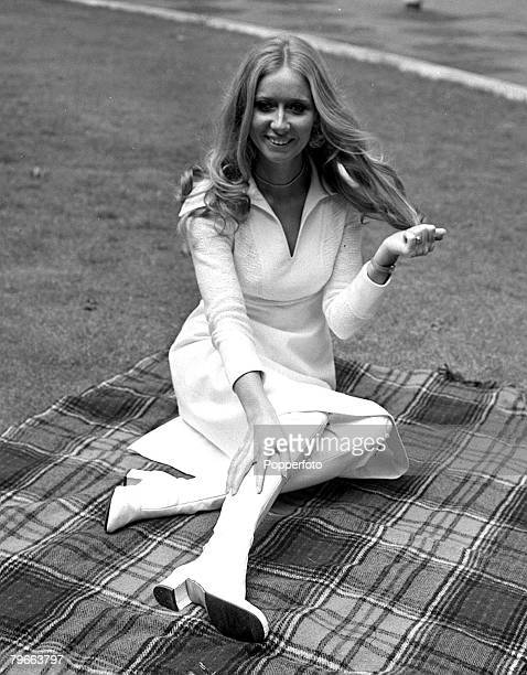 London England 29th July 1970 Irish pop singer Clodagh Rodgers sitting on a tartan picnic blanket in London wearing a white dress and knee high white...