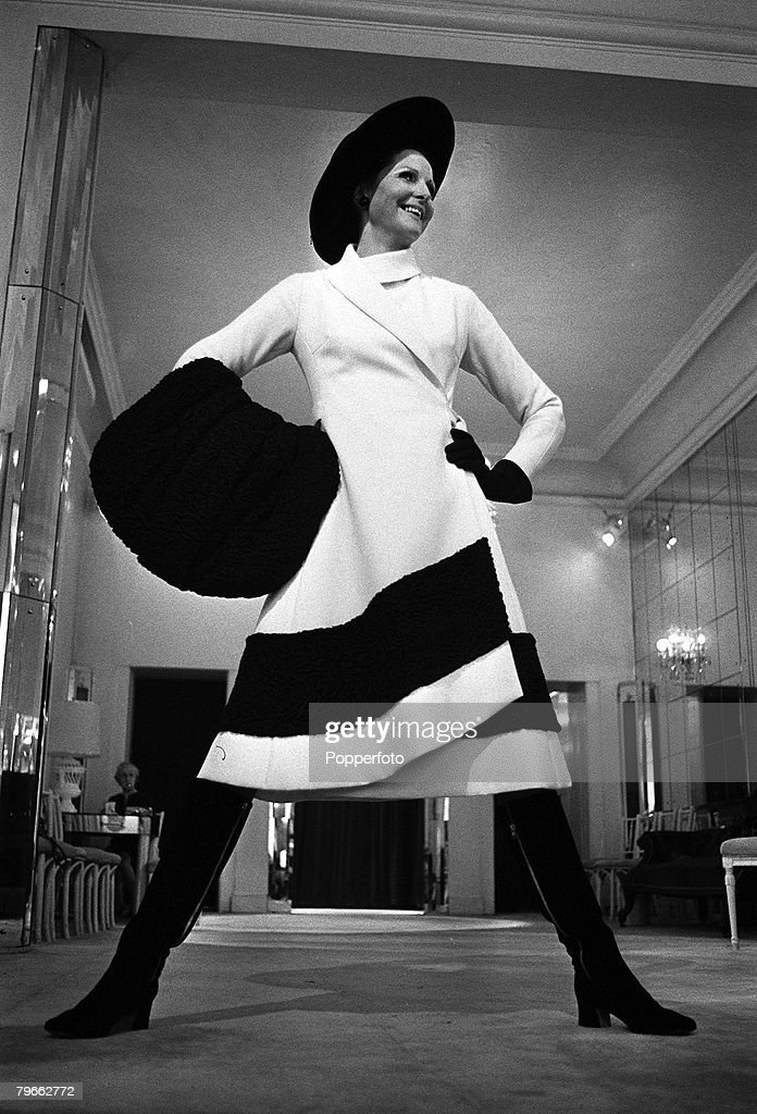 London, England, 2nd September 1970, , A model stands in Norman Hartnell+s Salon wearing one of his designs, +White Russia+ is a white fitted coat with asymmetric hem, bordered with black Persian lamb and worn with a matching lamb muff, a black velvet hat and knee length zipped boots