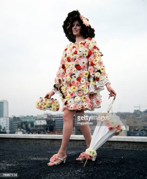 London England A model is pictured wearing a dress decorated with flowers and matching handbag hat and umbrella