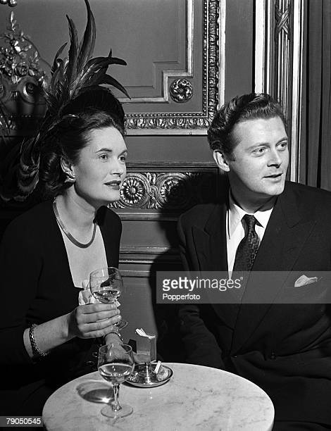 London England A picture of British actress Margaretta Scott wearing a feathered hat enjoys a drink with actor Emrys Jones at the 21st Birthday party...