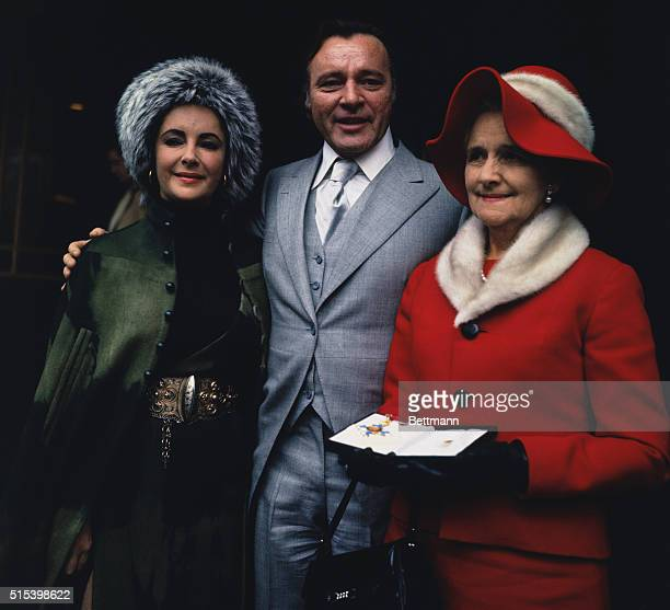 London, England: Actor Richard Burton on his 45th birthday, poses with his wife Elizabeth Taylor and sister, Mrs. Celelia James, after he received a...