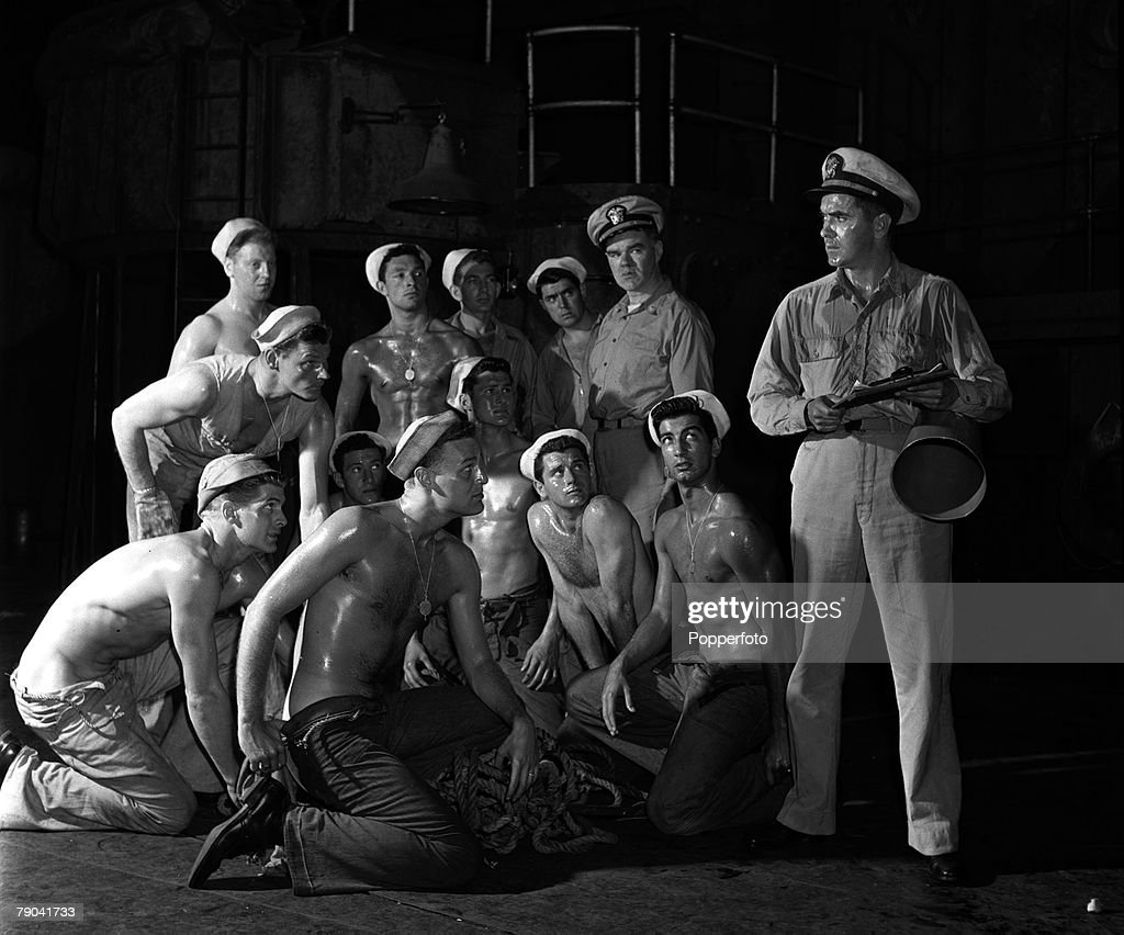 London, England. 1950. American actor Tyrone Power (right) is pictured in a scene from the play 'Mister Roberts' at the Coliseum Theatre, as the rest of the cast look on. : News Photo