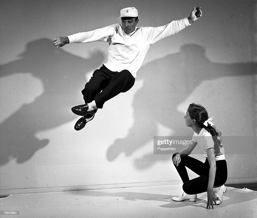 London, England. 1955. American dancer, choreographer, actor and director Gene Kelly is pictured demonstrating for 13 year old schoolgirl Julia Puccini. : News Photo
