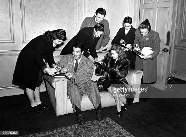 1947 London England American film star Robert Taylor and his actress wife Barbara Stanwyck sign autographs for their fans during a visit to London