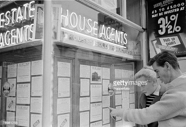 London England British film and movie actress Shirley Eaton looks in an estate agent window with her fiancee Colin LentonRowe They point at a...