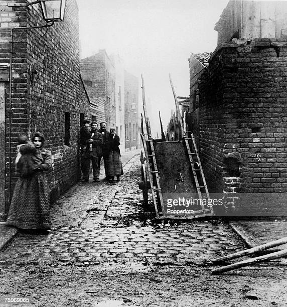 London England circa 1900 Family groups stand in the streets of the slum areas of Westminster London at the turn of the century