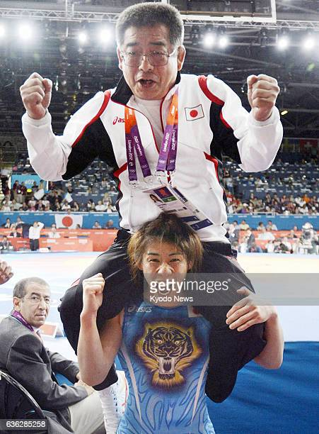 London, England - File photo taken in August 2012 shows Japan's Saori Yoshida celebrating with her father and coach Eikatsu on her shoulders after...