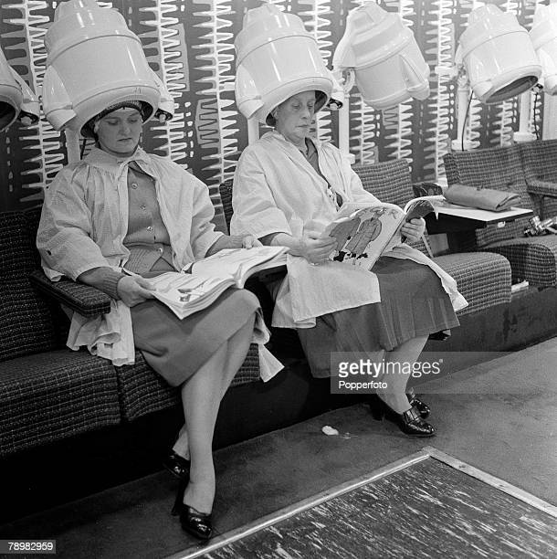 London, England, Ladies at a hair salon, While their hair is being dried thay read magazines