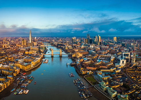 London, England - Panoramic aerial skyline view of London including Tower Bridge with red double-decker bus, Tower of London, skyscrapers of Bank District 1028621910