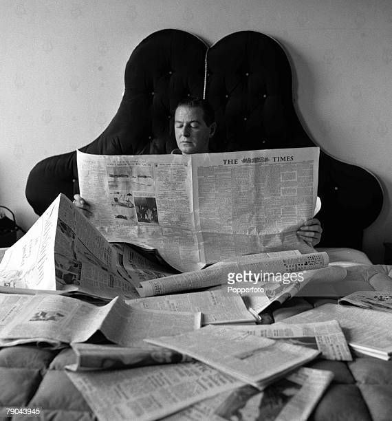 English playwright and screenwriter Terence Rattigan is pictured at his Eaton Square flat reading a newspaper in bed