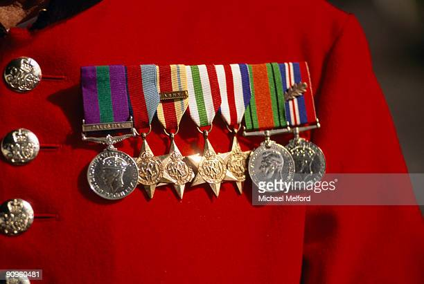 Medals adorn the breast of a red military uniform.