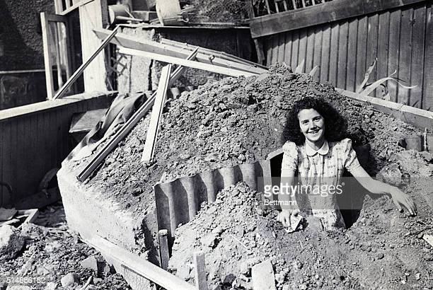 8/26/1940 London England Saved bt air raid shelter A housewife emerging from an air raid shelter in a Southwest London suburb after a Nazi bomb fell...