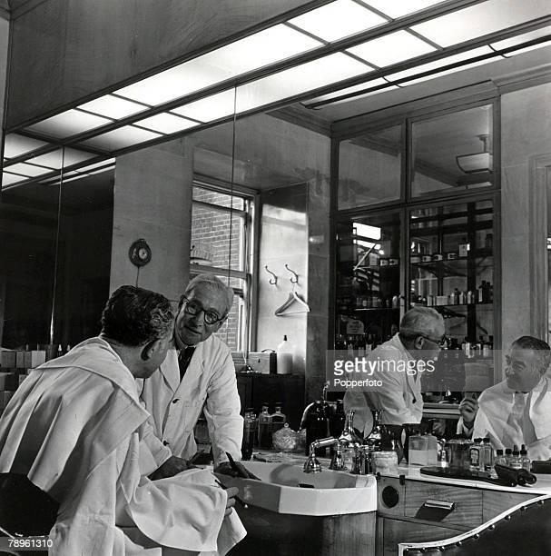 London England The Ritz Hotel Author Michael Arlen is attended to by the Hotel's resident barber Mr Albert Coleman in the small Barbershop in the Ritz