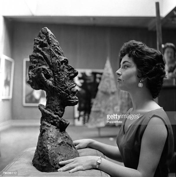 London England Vicky Darnell a show girl at the Windmill Theatre inspects a head by the Italian sculptor artist and author Alberto Giacometti during...