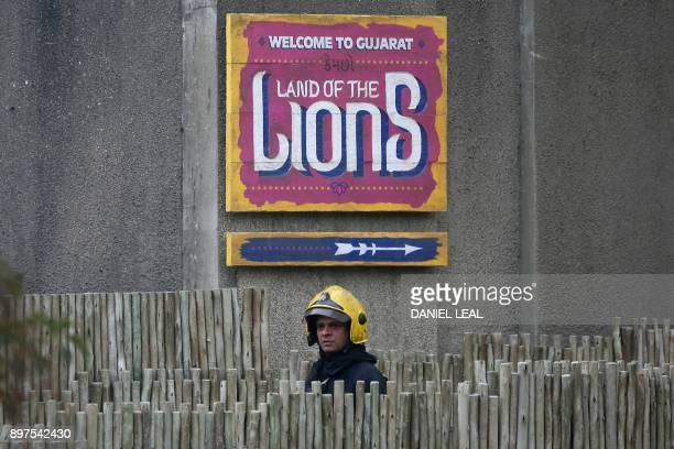 A London Fire Brigade firefighter attends to help control a fire that broke out at a cafe and shop at London Zoo in London on December 23 2017 A fire...