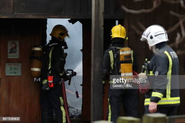 London Fire Brigade firefighters attend to control a fire that broke out at a cafe and shop at London Zoo in London on December 23 2017 A fire broke...