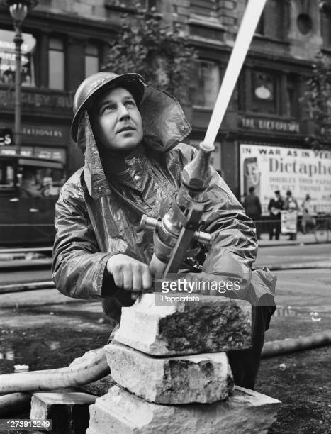 London Fire Brigade fireman aims a high pressure water hose on to a fire burning in Kingsway following a German Luftwaffe air raid over London during...