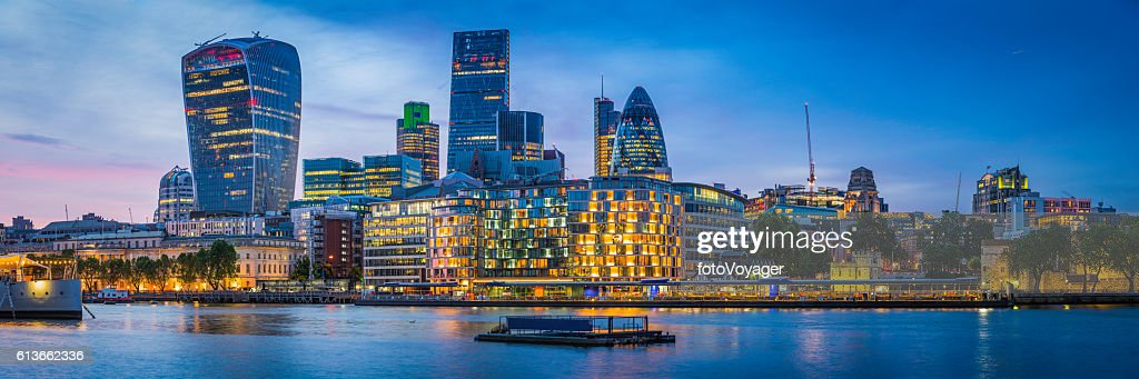 London futuristic skyscrapers glittering at sunset overlooking River Thames UK : Stock Photo