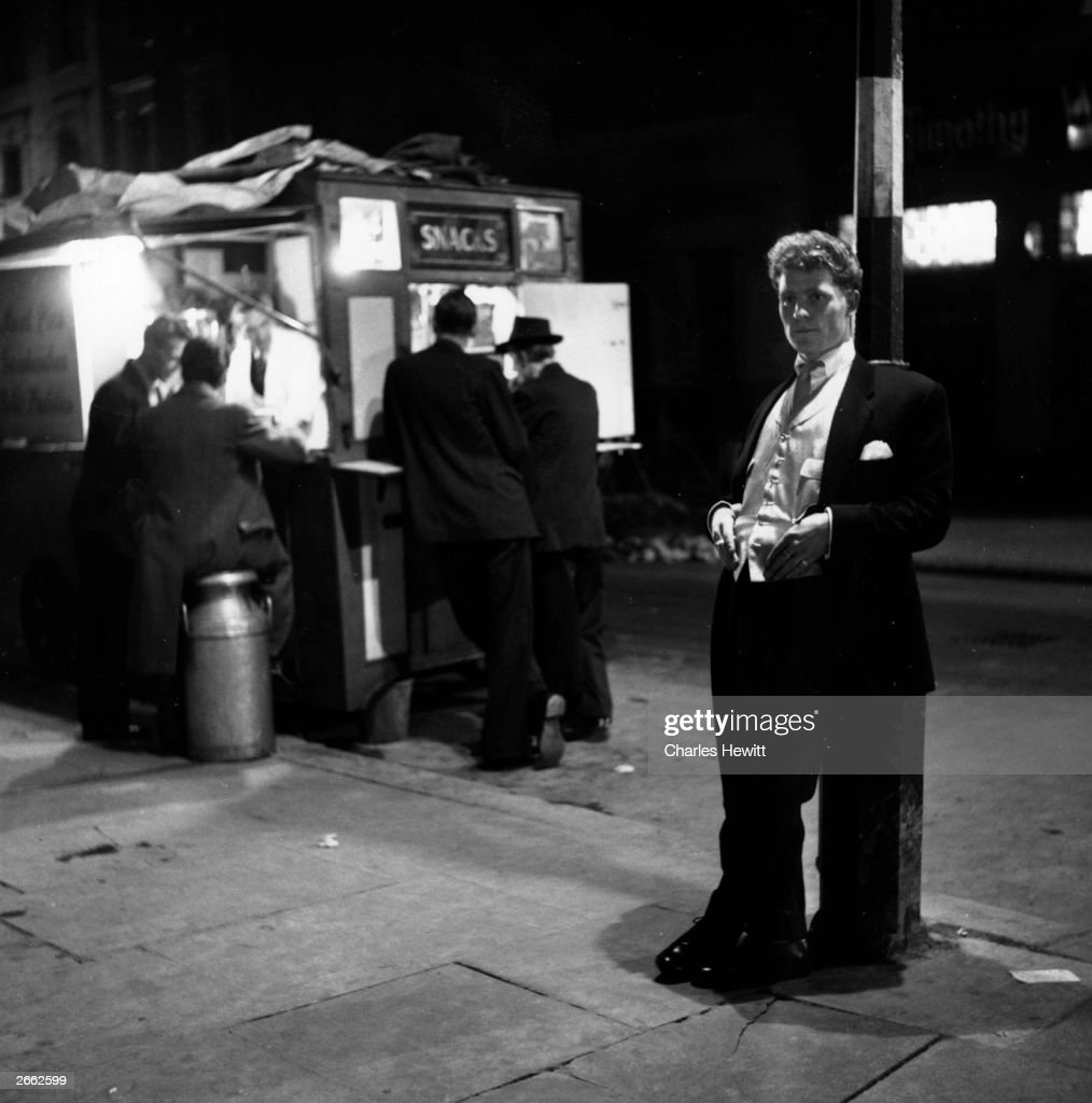 London gang member Colin Donellan lounges outside a coffee stall which is a favourite meeting-place for boy gangsters. Original Publication: Picture Post - 6729 - The Making Of Boy Gangsters - pub. 1953