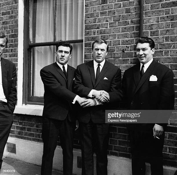 London gangster twins Ronald and Reginald Kray link hands with their brother Charles after the twins had been found not guilty on a menaces charge...