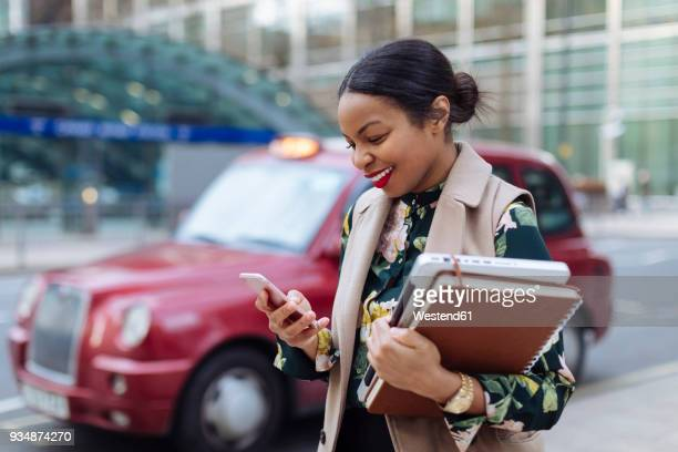 uk, london, happy businesswoman looking at cell phone - on the move stock pictures, royalty-free photos & images