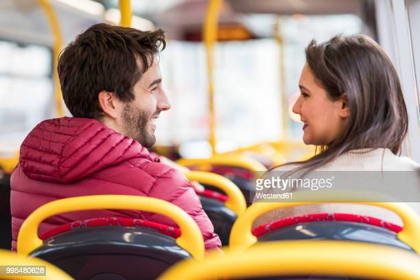 uk, london, happy young couple sitting side by side in bus - side by side stock pictures, royalty-free photos & images