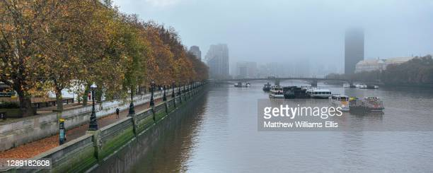 London in Coronavirus Covid-19 lockdown with person running and jogging along River Thames on South Bank with autumn trees in atmospheric misty...