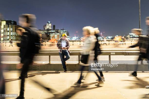 uk, london, man looking at his phone with blurred people walking on the pavement - pedone ruolo dell'uomo foto e immagini stock