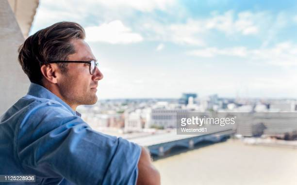 uk, london, man looking at the city on a roof terrace - ein mann allein stock-fotos und bilder