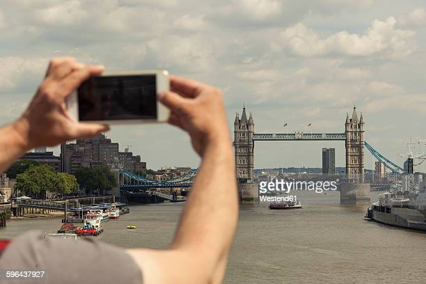 UK, London, man taking photo of Tower Bridge with his smartphone