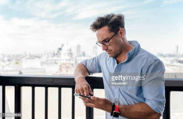 uk, london, man using cell phone on a roof terrace - rolled up sleeves stock pictures, royalty-free photos & images
