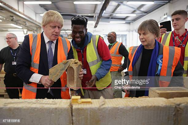 London Mayor Boris Johnson and Angie Bray Conservative candidate for Ealing Central and Acton get a lesson in bricklaying from Ealing Hammersmith and...