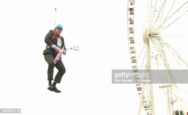 London Mayor Boris Johnson as he is left hanging in midair after he got stuck on a zipwire at an Olympic event at Victoria Park in the capital