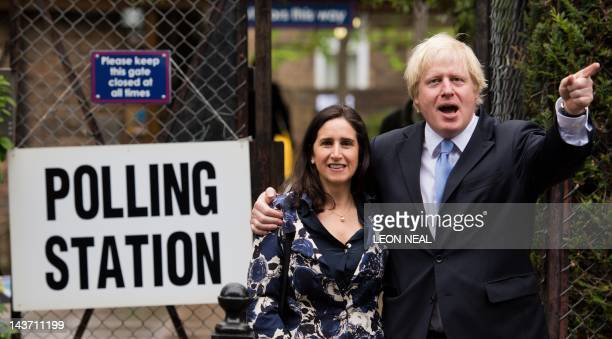 London Mayor Boris Johnson gestures as he stands with his wife Marina Wheeler after casting his vote in the local elections at a polling station in...