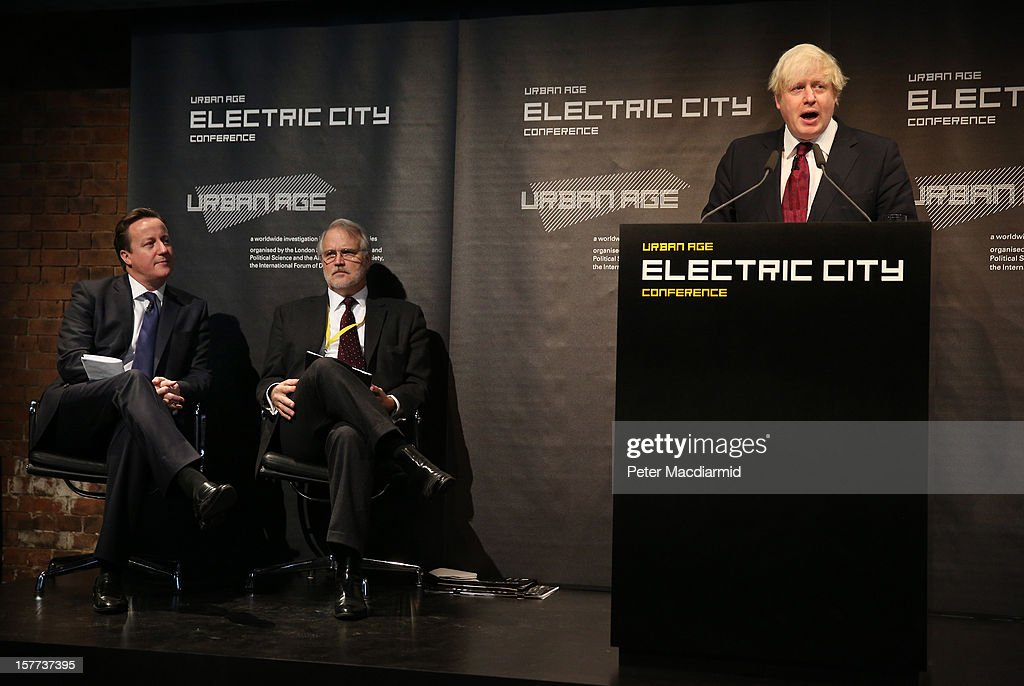 London Mayor Boris Johnson (R) is watched by Prime Minister David Cameron (L) and Craig Calhoun (2L), Director of The London School of Economics as he speaks at the The Electric City Conference on December 6, 2012 in London, England. The conference is looking at how the combined forces of technological innovation and the global environment crisis are affecting urban society.