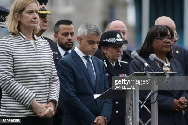 London Mayor Sadiq Khan bows his head flanked by Home Secretary Amber Rudd and Shadow Home Secretary Diane Abbott during a vigil in Potters Fields...