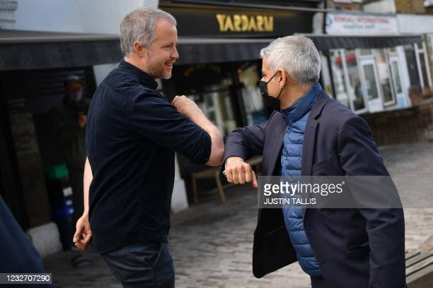 London Mayor Sadiq Khan bumps elbows with a local businessman as he campaigns ahead of the London mayoral election, in Waltham Forest, northeast...