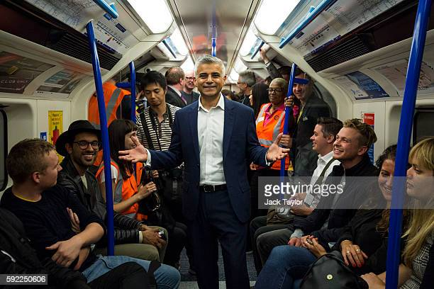 London Mayor Sadiq Khan extends his hands as his stand between passengers in the first Night Tube train along the Victoria line on August 20 2016 in...