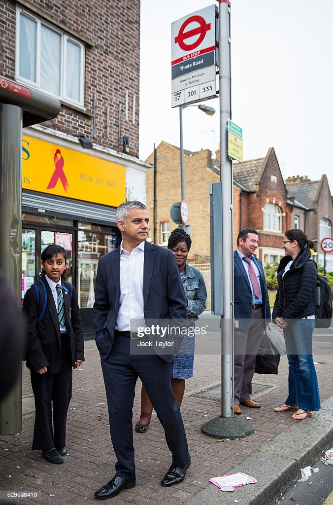 London Mayor Sadiq Khan (2nd L) waits at a bus stop after leaving his home in Tooting on May 9, 2016 in London, England. Mr Khan begins his first day at his City Hall office after winning the race to become London's Mayor with 56.8% of the vote.
