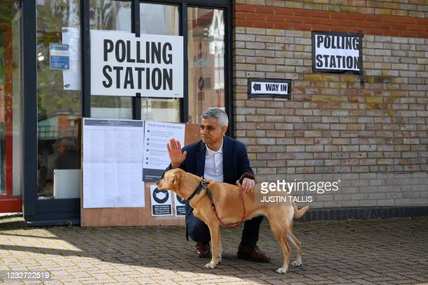 London Mayor Sadiq Khan waves to voters as he poses with his dog Luna on his arrival at a polling station in London to cast his vote in local...