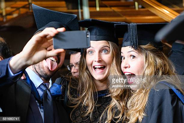 London, mixed group of university students posing for a selfie on graduation day, using mobile phone