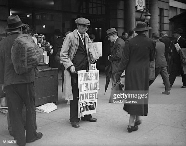 London newspaper vendor selling the Evening Standard announcing the Munich Summit: 'Chamberlain, Hitler, Duce To Meet'.