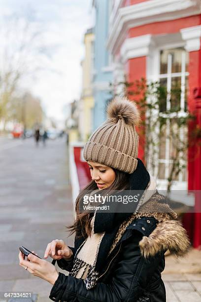 UK, London, Notting Hill, young woman looking at her smartphone