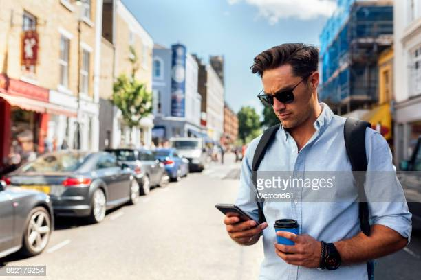 UK, London, Nottinghill, man looking at smartphone